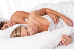 Blond woman and brunette sleeping Stock Photos