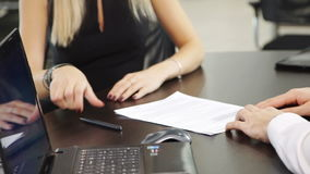 Blond woman buyer signs contract to buy car in office center. Agreement on white sheets of paper lying on table in front of client. close up shot of hands of stock footage