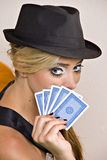 Blond woman with cards. Beautiful young blond woman holding playing cards near face and wearing black hat Royalty Free Stock Photo