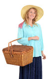 Blond woman carrying picnic basket Stock Photo