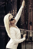 Blond woman at the cast iron fence Stock Photos