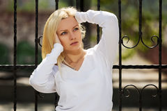 Blond woman at the cast iron fence Royalty Free Stock Image