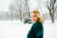 Blond woman in checked sweater outside in winter nature Stock Photo