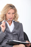 Woman chewing pen Stock Photo