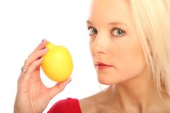 Blond woman with a citron. Young blond woman showing a citron royalty free stock image