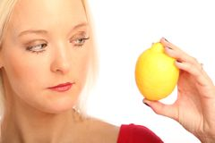 Blond woman with a citron. Young blond woman showing a citron royalty free stock images
