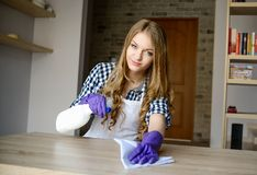 Blond woman cleaning table at home Stock Photo