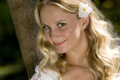 Blond woman closeup. Horizontal closeup of a smiling young blond woman in wedding attire with a white flower in her hair, taken in an outdoor setting stock photo