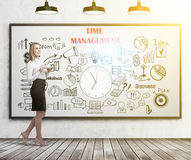 Blond woman with a coffee, time management. Side view of a blond businesswoman holding a white coffee cup. She is standing in a classroom with a whiteboard. Time Stock Photography