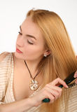 Blond woman combing Royalty Free Stock Photography
