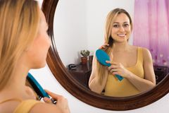 Blond woman combing looking in mirror. In bedroom Stock Image