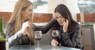Blond woman comforting friend over glass of wine stock footage
