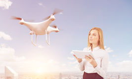 Blond woman controls a drone in city Stock Photo