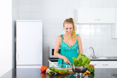 Blond woman cooking Royalty Free Stock Photos