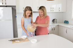 Blond woman cooking and baking happy together with sweet adorable mini chef little girl at home kitchen in mother and daughter lov Royalty Free Stock Photos