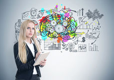 Blond woman with a copybook, brain cogs Royalty Free Stock Photography