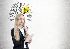 Blond woman with a copybook, questions, bulb. Close up stock photography