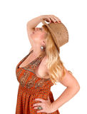 Blond woman with cowboy hat. A portrait image of a pretty blond woman in a dress wearing a cowboy Stock Photo