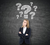 Blond woman with crossed arms and question marks royalty free stock photo