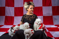 Blond woman in crown with fluffy puppies Stock Photo