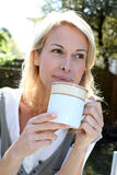 Blond woman with cup of tea Royalty Free Stock Photography