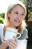 Blond woman with cup of tea Royalty Free Stock Image