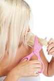 Blond woman cutting her hair Royalty Free Stock Photography