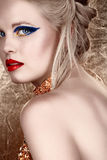 Blond woman with dark eyeshadow. Beautiful blond with hair in upstyle wearing dark fashion eyeshadow and red lips looking over shoulder on gold background in Royalty Free Stock Photo