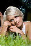 Blond woman daydreaming while laying on grass Stock Image