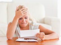 Blond woman in despair holding a letter Stock Images