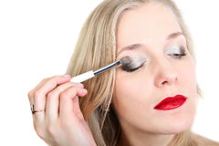 Blond woman  does make-up Royalty Free Stock Image