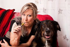 Blond woman with dog and electric cigarette Royalty Free Stock Images