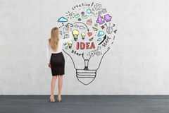 Blond woman drawing business idea sketch inside a light bulb. Rear view of blond woman drawing business idea sketch inside a giant light bulb on concrete wall royalty free stock image