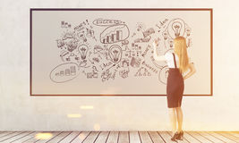 Blond woman is drawing business sketches on whiteboard, toned Royalty Free Stock Images