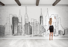 Blond woman drawing cityscape on concrete wall Royalty Free Stock Photography
