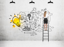 Blond woman drawing a plan on ladder Stock Images