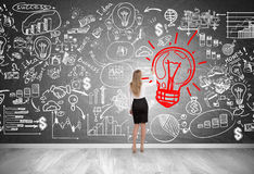Blond woman drawing red light bulb Stock Photo
