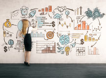 Blond woman drawing start up sketch. Side view of blond woman drawing startup sketch on concrete wall. Concept of business development. Toned image royalty free stock image