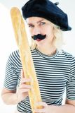 Woman dressed as french man with mustache and beret holding baguette. Blond woman dressed as a french man with mustache and beret holding a baguette stock image