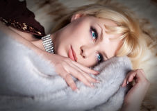 Blond woman dressed in fur and lingerie lying Stock Photography