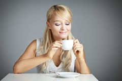 Blond woman is drinking a cup of coffee or tea Stock Photo