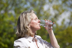 Blond woman drinking a glass of water. A beautiful mature blond woman  drinking a glass of water Royalty Free Stock Photography