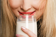 Blond woman drinking milk Stock Image