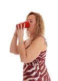 Blond woman drinking from red coffee mug. A image of a blond woman in a summer dress standing in profile drinking Stock Photos