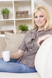 Blond Woman Drinking Tea or Coffee At Home. A beautiful young blond woman drinking tea or coffee from a white mug sitting at home on a her sofa Stock Image