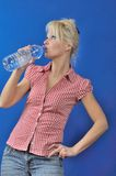 A Blond woman drinking water Stock Photography