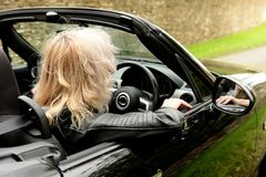Blond woman driving car. Rear side view of blond woman driving black car down countryside road stock image