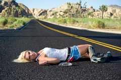 Blond woman drunk laying on highway Stock Photography