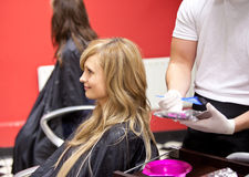 Blond woman dying her hair Stock Images