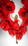 Blond woman in dynamic beautiful red dress Royalty Free Stock Photo